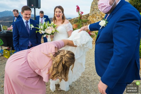 Wedding photo from a Malibu Solstice Vineyard, Malibu, California outdoor event as The bridesmaids lift the bride's dress to find a dress loop