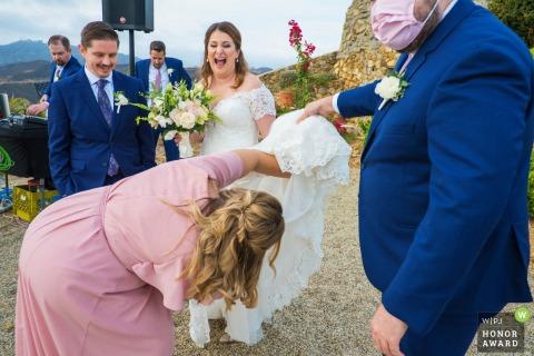 Trouwfoto van een Malibu Solstice Vineyard, Malibu, Californië openluchtevenement terwijl de bruidsmeisjes de jurk van de bruid optillen om een jurklus te vinden