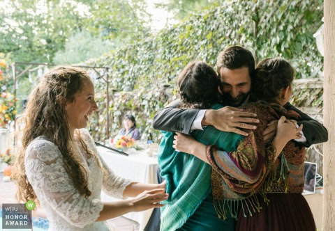Wedding photography from Long Island, NY showing A groom hugs the bride's two sister's while the bride smiles joyfully