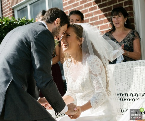 New York wedding photo from Long Island as The bride and groom put their foreheads together joyfully after seeing each other for the first time on their wedding day during the b'deken