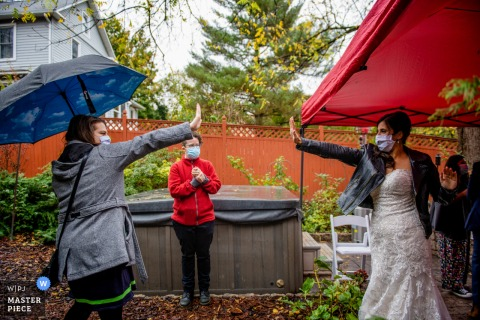 Rockville Backyard Wedding photo of bride and one of her best friends go in for a socially distanced hi-five at the reception