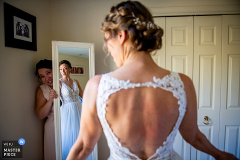 Virginia Farm wedding photography of bridesmaid holding the mirror up so the bride can get a good look at herself before she goes off for the first look.