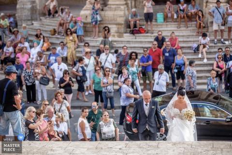 Fotografia de casamento da noiva na igreja da Sicília subindo as escadas para a cerimônia com um grande grupo de turistas assistindo