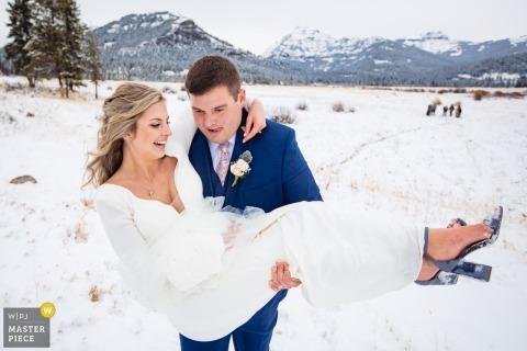Winterhochzeitsfotografie des Yellowstone-Nationalparks im Schnee von Braut und Bräutigam während der Rezession
