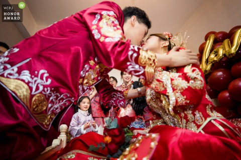 Hangzhou groom kisses his bride as young children watch on