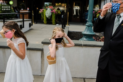 New York wedding image of two little flower girls and the father of the bride adjusting their medical masks while waiting outside for the trolley in Saratoga Springs