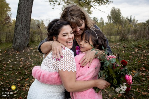 Ontario Backyard wedding photo showing the Bride gets hugs from her Aunt and Niece after the ceremony