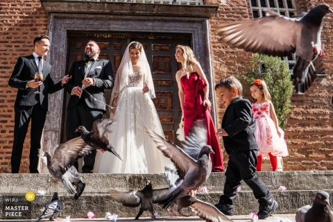 Sofia, Bulgaria, st. Sofia church wedding photography showing The newlyweds leaving the church under attack by pigeons
