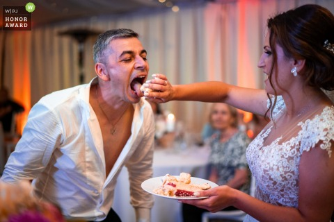Bulgarian couple during the wedding cake feeding at the reception