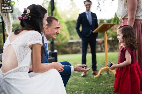 French wedding photographer captured a young girl bringing the rings to the bride and groom during the ceremony
