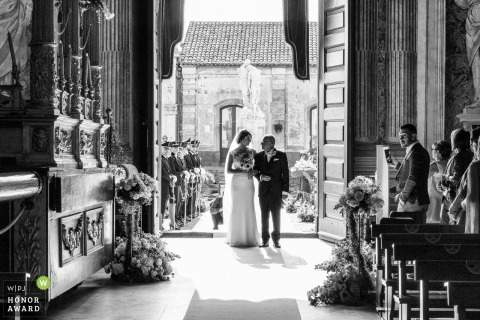 Italy wedding image captured of the bride's father as he freezes at the church entrance and their gazes meet for an intimate moment at the Basilica di Santa Caterina Alessandrina