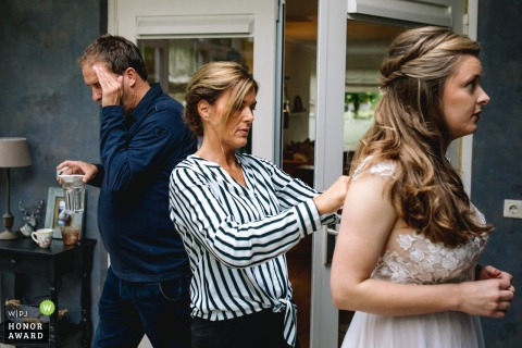 Netherlands bride is getting buttoned up by her mother as dad passes through covering his eyes