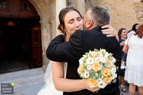 French wedding photographer captures the bride embracing her father at the Church of Bagnols sur Cèze