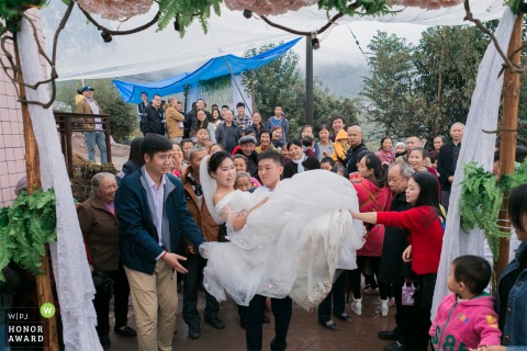 ChongQing wedding photographer captures the bridegroom carrying the bride into the new house, attracting villagers to watch