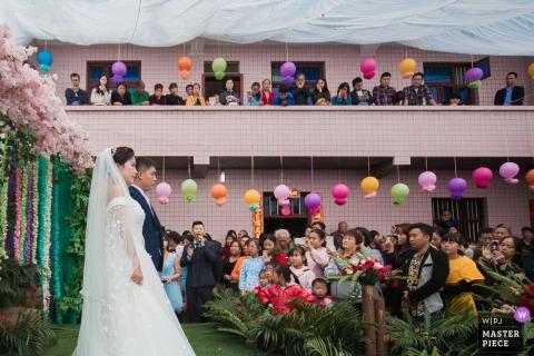 China Home wedding photo of La nuova coppia e la loro cerimonia di matrimonio sul palco allestito nel loro cortile, e gli abitanti del villaggio sono venuti a vedere la cerimonia