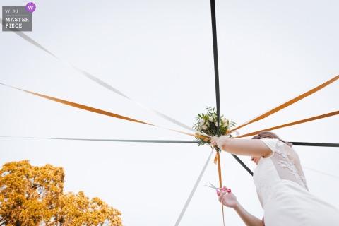 Les Cabanes dans les Bois Domaine de Fourtou wedding photography of the bouquet and ribbon cutting ceremony outdoors