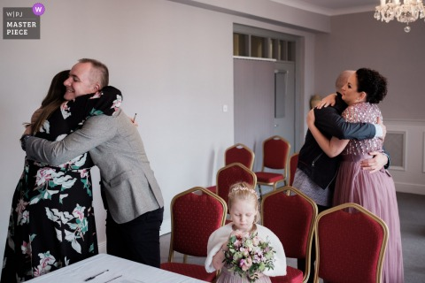 The Royal Hotel, Bray, Ireland wedding photography showing the daughter remains fascinated by her bouquet even after the ceremony has finished as The two of them hug their witnesses