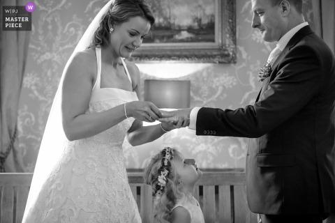 Kasteel Hackfort, fotografia di matrimonio di Vorden che mostra la ragazza dei fiori che partecipa allo scambio di fedi da parte di sua madre e suo padre