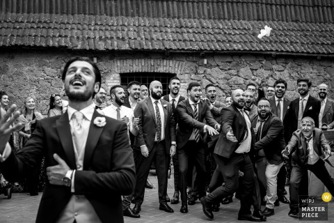 Casale Torre Sant'Anastasia wedding photography of the groom and Male bridal party at the garter throwing