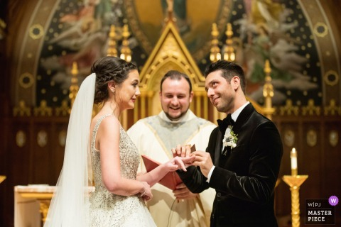 Seton Hall Chapel, Seton Hall University, New Jersey wedding photo created as the groom struggles to get ring on bride