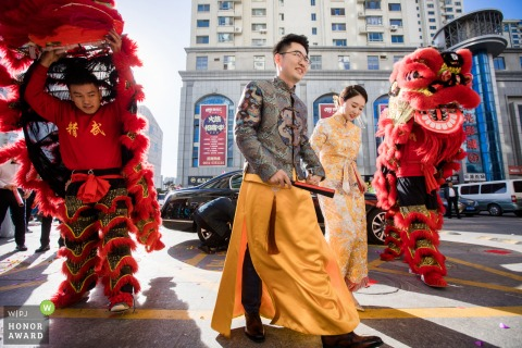 Outdoor urban wedding photography from Weihai, China showing the couple walking the streets in Chinese traditional customs