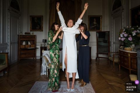 Fotografia di matrimonio di hotel Auvergne-Rhône-Alpes creata mentre la sposa si infila il suo abito