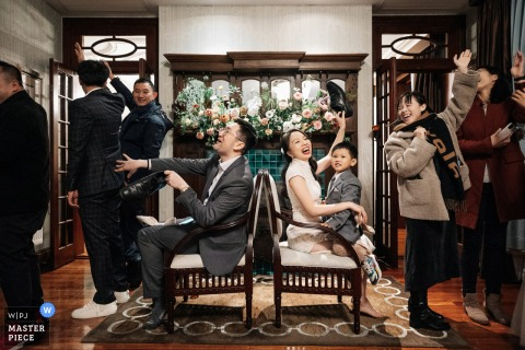 Shanghai, China Hotel wedding photo illustrating Relatives and friends play shoe games with the bride and groom