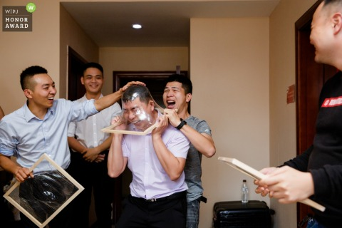 Fujian, China wedding photography of the groom and groomsmen playing door games with stretched plastic on frames