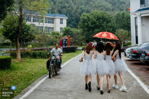 Fujian, China wedding photography of bridesmaids walking outdoors under red umbrella