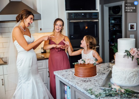 Omaha, Nebraska wedding photo at home of the flower girl trying to get into groom's cake, and the bride and bridesmaid caught her