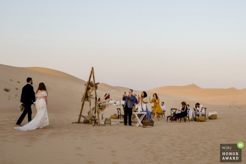 UAE wedding photo from a Dubai Desert Location showing the Bride and Groom returning to the Party in the sand