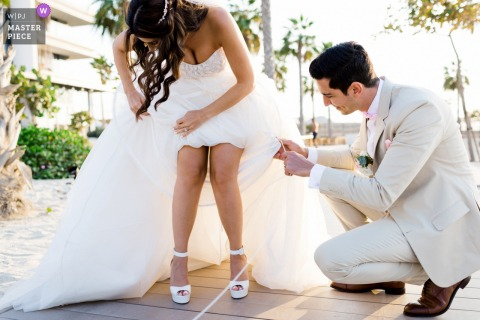 Nikki Beach Dubai wedding photography of the Groom helping the Bride fix her dress