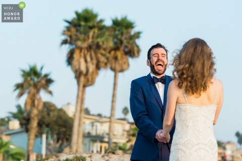 California outdoor beach wedding photo from Carpinteria as A groom laughs during his vows on his intimate beach ceremony