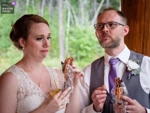 West Glacier, Montana, fotografia di matrimonio che mostra la sposa e lo sposo assaggiare i diversi antipasti di pancetta preferiti. A causa del COVID-19 tutti gli antipasti dovevano essere confezionati singolarmente