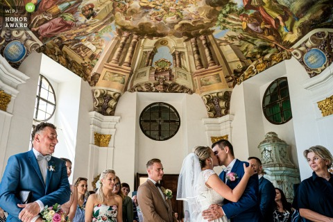 Indoor wedding ceremony photo from Žďár nad Sázavou Chateau showing the first kiss under the epic ceiling