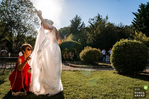 French wedding photography from Ferme De Bouchemont showing the brides dress becoming a Fly trap outdoors in the sun