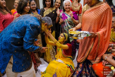 Comunidade Hindu de Portugal, Lisboa, Portugal wedding photo showing the The bride's best man was also blessed by the bride at the Pithi ceremony, a blessing ceremony for the bride, under the look of all bride's closest family