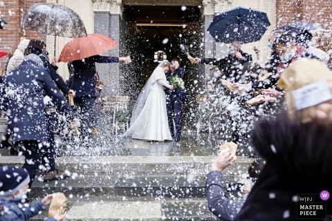 Basilica di San Magno, Legnano, Italia foto de boda que muestra una tormenta de arroz sobre los recién casados