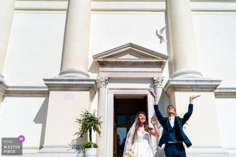 Pordenone, Italia fotografia di matrimonio che mostra il volo della colomba fuori dalla chiesa