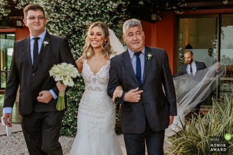 Fotografía de boda al aire libre de Casa dos Noivos, Xangri-lá, Brasil que muestra a la novia entrando con ambos padres mientras una amiga se arregla el velo