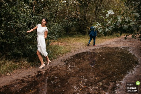 Antwerpen wedding photography from Near the reception venue as The bride tries to get passed a puddle that's blocking the road, while the husband already gave up and is heading towards the other side