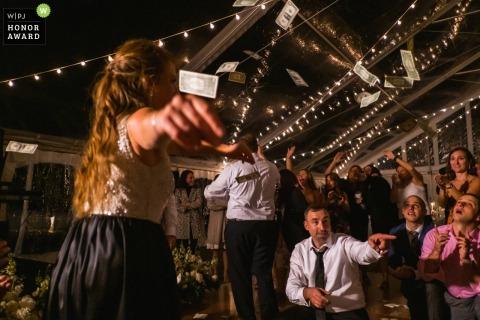 Afbeelding van de huwelijksreceptie in Pennsylvania van een gast die danst terwijl mensen dollarbiljetten in de lucht gooien in Boiling Springs