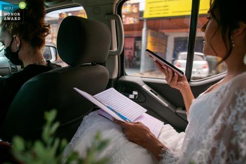 Noiva goiana sentada no banco de trás de um carro enquanto viajam pela cidade no dia do casamento