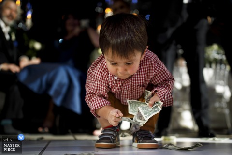 Seawell Ballroom wedding photo showing A young boy picking up dollar bills off the dance floor during a greek wedding