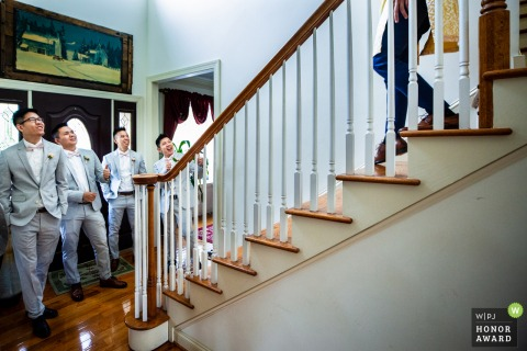 Virginia wedding photographer captured the moment where the groomsen waited at the bottom of the stairs excitedly as the groom descends wearing Vietnamese traditional closthing for the first time