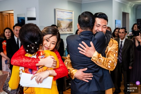 Virginia Home Ceremony fotografia di matrimonio della sposa e dello sposo che abbraccia i loro genitori durante la cerimonia del tè
