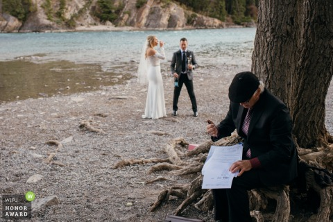 Bow Falls, Banff wedding elopement photo captured of the ceremony mirage commissioner signing the documents