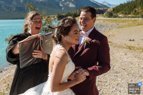 Lake Minnewanka, Banff National Park, AB, Canada fotografia di matrimonio che mostra che la sposa non ha potuto mettere un anello al dito dello sposo