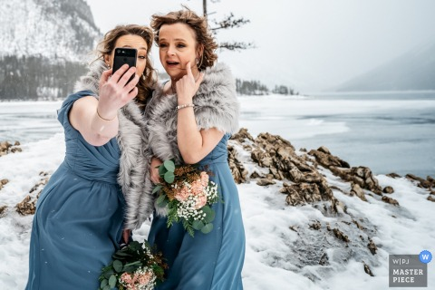 Lake Minnewanka, Banff National Park, AB, Canada wedding photography of Bridesmaids taking selfie photo in very cold weather