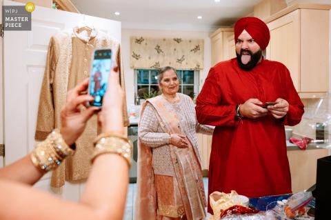 Thuis trouwfoto in Oxford, VK gemaakt terwijl de bruidegom zich klaarmaakt, zijn zus maakt een telefoonfoto van hem